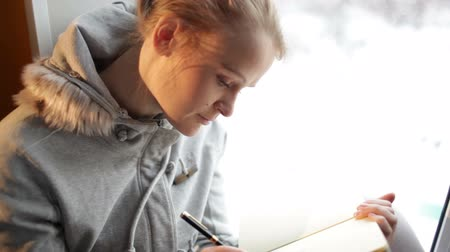 журнал : Young beautiful girl writing in her journal and daydreaming. Стоковые видеозаписи