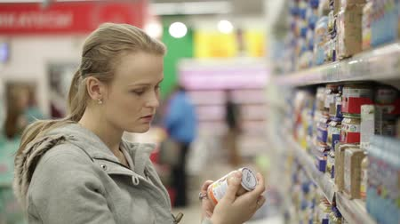 продукты : Young woman is choosing food for her child in the shopping center. No visible trademarks or logos. Close up shot with shoppers in background.