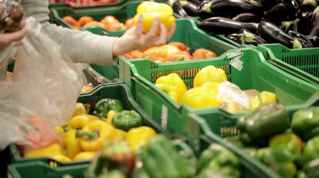 biber : Woman in a supermarket choosing vegetables at the vegetable shelf. Stok Video