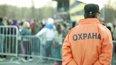 безопасность : Back of a security guard in front of blurred crowd