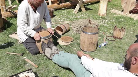 barrell : Moscow historical festival Times and epoch in Colomna. Two workers are making a barrell in a traditional style.