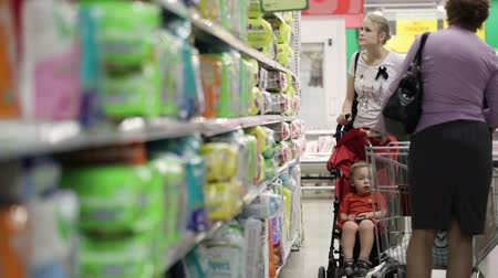 sáně : Mother with her boy in baby carriage in the supermarket