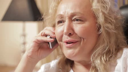falar : Middle-aged caucasian woman speaking on the mobile phone emotionally