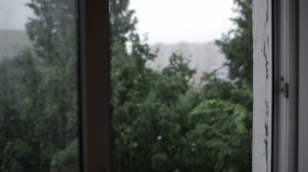 ulewa : Heavy rain. Focus pulling from window to the building.