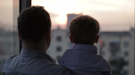 otec : Father and son on the balcony watching the sunset. Close up.