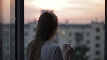 кофе : Young girl on the balcony watching the sunset and drinking tea. Middle shot Стоковые видеозаписи