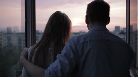 стоять : Young couple on the balcony watching sunset. Middle shot. Стоковые видеозаписи
