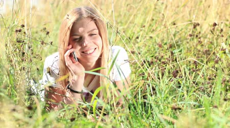outside : Beautiful girl is lying in the grass and talking on the phone in the city park at summer.