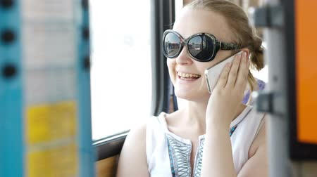 inside bus : Happy attractive young woman wearing sunglasses talking on her smartphone and smiling with delight while travelling by bus