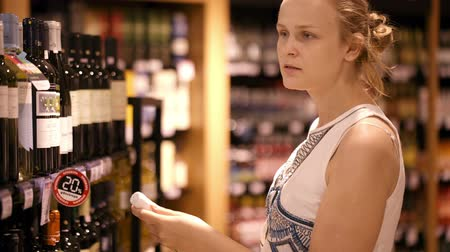 beyaz şarap : Woman shopping for wine or other alcohol in a bottle store standing in front of shelves full of bottles with a serious expression as she tries to make up her mind Stok Video