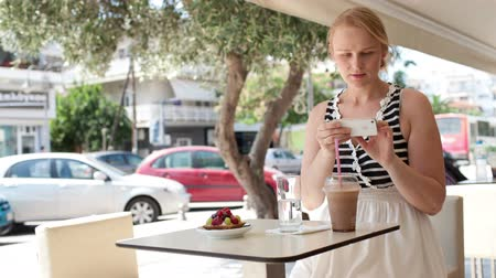 meal : Attractive woman taking picture of a pastry on her smart phone as she sits at a table at an open-air restaurant enjoying refreshments Stock Footage