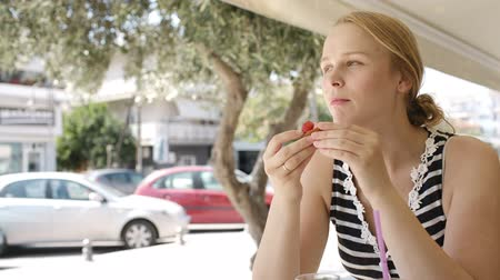 meal : Attractive young blond woman eating refreshments in a cafeteria overlooking an urban street