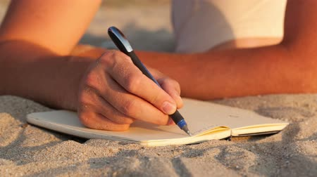 сценарий : Man writing in his diary at the beach while lying on the golden sand, close up view of the book and his hand holding a pen