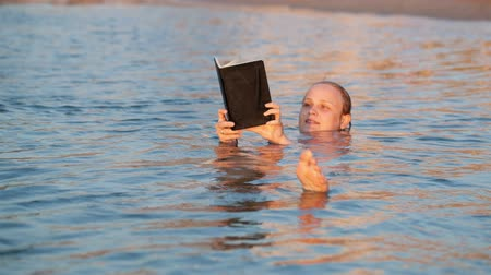 плавающий : Woman smiling as she reads a book while swimming floating on her back in the water holding the book in the air