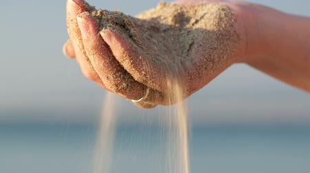 drží se za ruce : Close up of the hand of a woman drizzling sea sand through her fingers against an ocean backdrop, conceptual image Dostupné videozáznamy