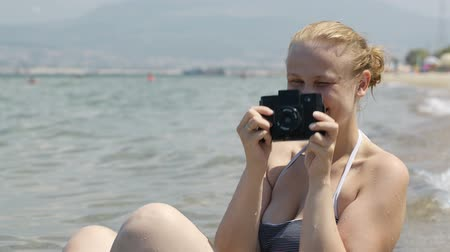 alma : Smiling woman in a bikini sitting on the beach at the edge of the water taking a photograph at the seaside with her vintage camera with plastic lens
