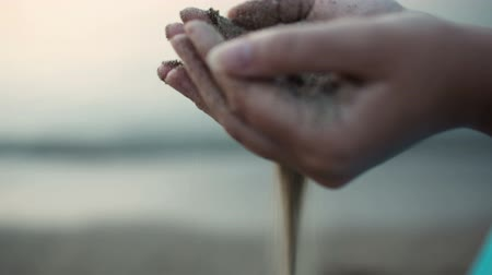 philosopher : Close up view of sea sand running through a womans hands against a blurred ocean backdrop with copyspace conceptual of a summer vacation