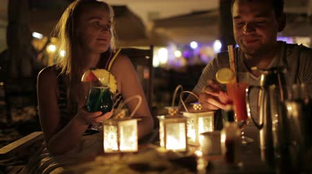 обедающий : Romantic young couple enjoying drinks in a date in an outdoor bar esplanade by night