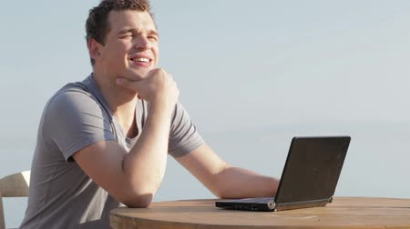 munka : Man typing on a small laptop computer as he sits enjoying the summer sunshine while on vacation allowing him to connect to the internet via wireless