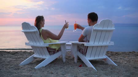 romantic : Romantic couple sitting in wooden deckchairs on the beach toasting the sunset clinking their cocktail glasses together, view from behind looking out to sea Stock Footage