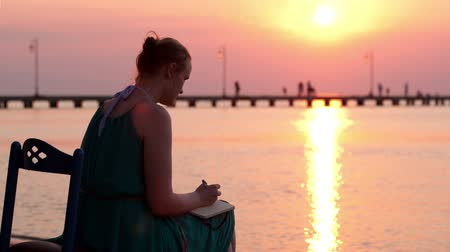 autor : Young woman sitting and writing something in her diary by the seashore during sunset
