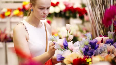 фокус : Beautiful young lady buying fresh flowers in a store or market choosing blooms for her decor at home Стоковые видеозаписи