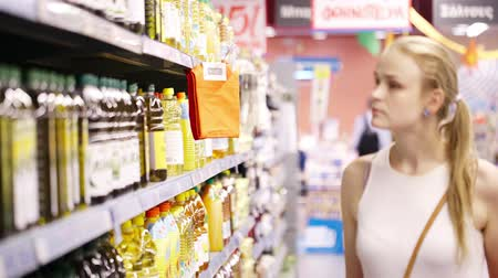 супермаркет : Young blond woman picking an olive oil bottle from the shelves of a supermarket and reading the label Стоковые видеозаписи