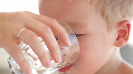 içme : Cute little boy drinkng a glass of fresh water being held by his mother as he quenches his thirst Stok Video