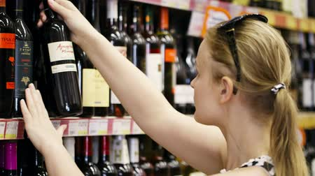 kırmızı şarap : Woman shopping for wine or other alcohol in a bottle store standing in front of shelves full of bottles Stok Video