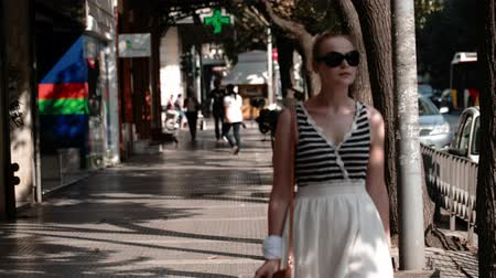 caminhada : Young woman in sunglasses walking under a covered urban arcade in a cool summer dress