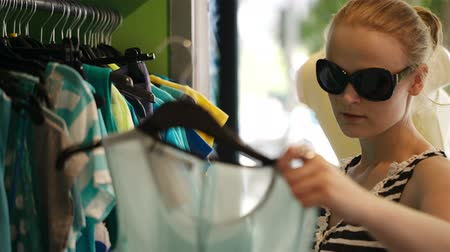 покупка товаров : Young woman in sunglasses choosing summer clothes hanging on the racks in the shop.