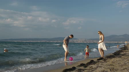três : Happy young parents and their little son playing football on the beach. Family vacation in summer.