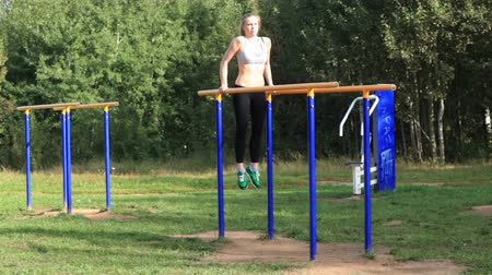 gymnasta : Athletic girl exercising on parallel bars on sports ground on bright summer day. Dostupné videozáznamy