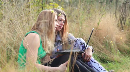 сестра : Two female friends sitting on the grass and talking online using laptop.