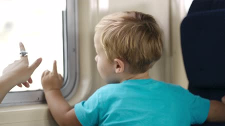 points of interest : Little boy in the train looking out the window, mother pointing somewhere and talking.