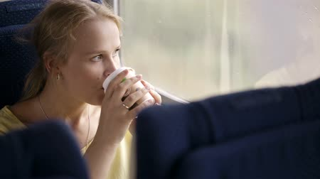 мысль : Pensive blond young married woman drinking coffee and looking out the window while traveling by train