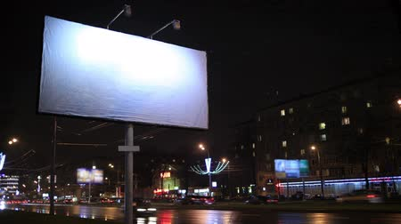 billboards : Time lapse of urban scene with an illuminated empty billboard on the side of a street with cars in motion and a block of flats in the background, by night
