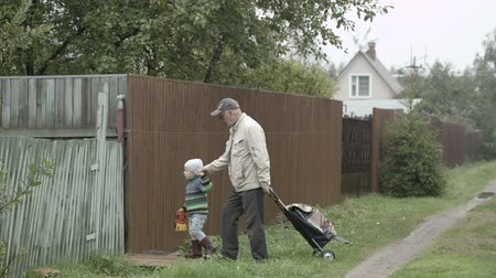 grandchild : Grandpa and his little grandson coming into house gate in the village. Old man rolling a trolley bag.