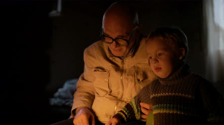 grandchild : Grandfather and grandson near fireplace at home with fire enlighting their faces. They talking and smiling. Stock Footage