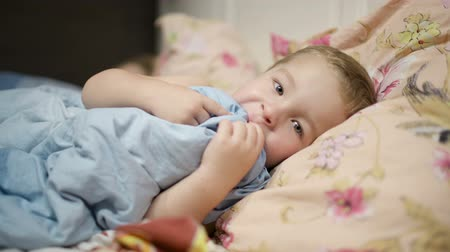время ложиться спать : Little boy in bed playing with the blanket, putting it into the mouth. Стоковые видеозаписи