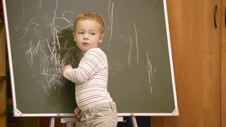 przedszkole : Creative little boy drawing on a chalkboard in a kindergarten classroom turning to look back over his shoulder for approval