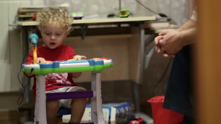 toy : Little boy playing toy piano and having fun. Man sitting near by. Stock Footage
