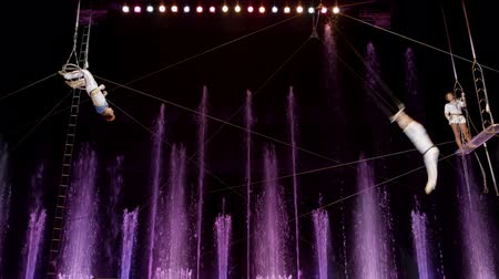 цирк : Aerial acrobatics perfomance in circus. Purple fountains in background. Acrobats fall at the end.