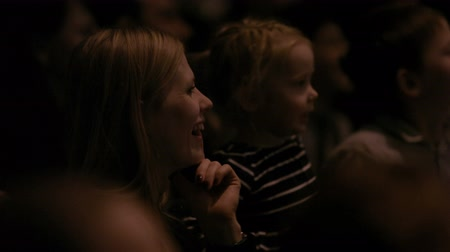 комедия : People sitting in the theatre or cinema with laughing young woman and little girl  in focus.
