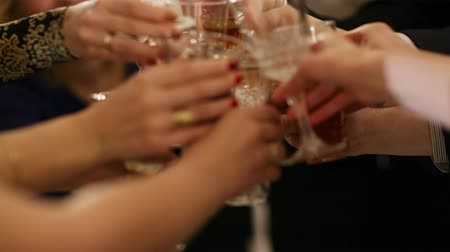 feliz ano novo : Group of people toasting at a celebration clinking their glasses together in congratulations , close up view of their hands Vídeos