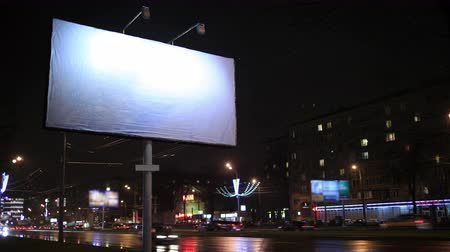 billboards : 4K footage of Time lapse urban scene with an illuminated empty billboard on the side of a street with cars in motion and a block of flats in the background, by night Stock Footage
