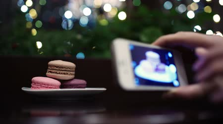 restoran : Macaroons on the table with following focus on female hand taking a picture of dessert using phone camera. Stok Video