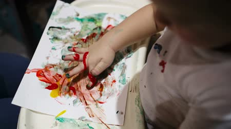 ručně malovaná : Little boy painting with colorful finger-paints. Activity for children.