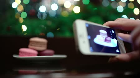 миндальное печенье : Macaroons on the table with following focus on female hand taking a picture of dessert using phone camera. Стоковые видеозаписи