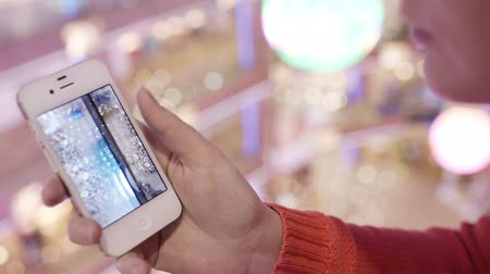 képek : Woman looking through the photos of Christmas tree in her smartphone with zooming of one of them.